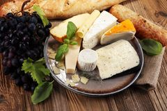 Cheese platter with different cheese on rustic plate.  Royalty Free Stock Photography
