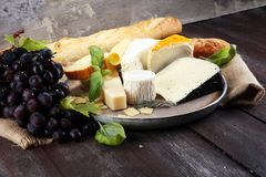 Cheese platter with different cheese on rustic plate.  Stock Photo