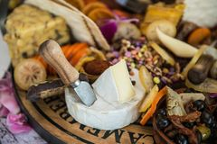 Cheese platter with different cheese types served with olives, fruits and nuts Stock Photos