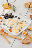 Cheese platter with different fruits and nuts  on the white wooden table vertical Stock Image