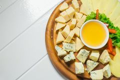 Cheese platter with different cheese, honey and vegetables royalty free stock photos