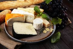 Cheese platter with different cheese on rustic plate.  Stock Photos