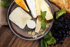 Cheese platter with different cheese on rustic plate.  Stock Photography