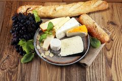 Cheese platter with different cheese on rustic plate.  Stock Images