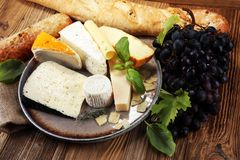 Cheese platter with different cheese on rustic plate.  Royalty Free Stock Images