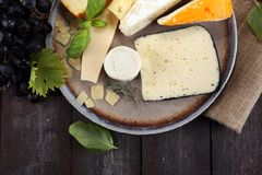 Cheese platter with different cheese on rustic plate.  Stock Image