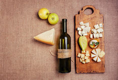 Cheese platter garnished with honey. Apple and bottle of wine on rustic wooden board Royalty Free Stock Image