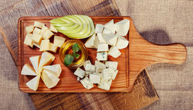Cheese platter garnished with honey and apple. On rustic wooden board Royalty Free Stock Images