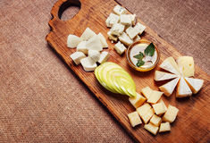 Cheese platter garnished with honey and apple. On rustic wooden board Royalty Free Stock Image