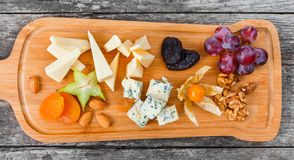 Cheese platter garnished with pear, honey, walnuts, grapes, carambola, physalis on cutting board on wooden background. Snacks and Wine appetizers set. Top view Stock Photo
