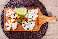 Cheese platter garnished on rustic wooden board. Cheese platter garnished with honey, apple and spice on rustic wooden board Royalty Free Stock Photo