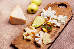 Cheese platter garnished on rustic wooden board. Cheese platter garnished with honey, apple and spice on rustic wooden board Stock Photo