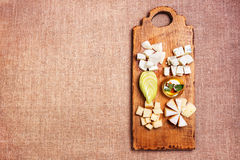 Cheese platter garnished on rustic wooden board. Cheese platter garnished with honey, apple and spice on rustic wooden board Stock Image