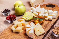 Cheese platter garnished on rustic wooden board. Cheese platter garnished with honey, apple and spice on rustic wooden board Stock Images