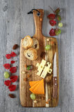 Cheese platter: Gouda cheese, green grapes and red autumn leaves Stock Photo