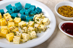 Cheese platter, Gouda, feta, blue pesto cheeses on white plate with herbs, olive oil, pomegranate and mustard sauces Royalty Free Stock Photos