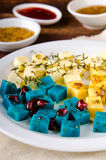 Cheese platter, Gouda, feta, blue pesto cheeses on white plate with herbs, olive oil, pomegranate and mustard sauces Royalty Free Stock Images