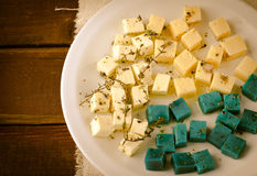 Cheese platter, Gouda, feta, blue pesto cheeses on white plate with herbs, olive oil, pomegranate and mustard sauces Stock Photos