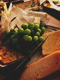 Cheese platter. Cheese and grapes on a board Stock Photos