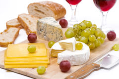 Cheese platter, grapes, bread and red wine on a wooden board Royalty Free Stock Image