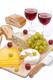 Cheese platter, grapes, bread and red wine on a wooden board Royalty Free Stock Photography