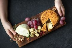 Cheese platter and hands of cheese maker. Cheese platter with assorted cheeses, grapes, nuts and hands of cheese maker on black background. Italian cheese and Royalty Free Stock Image