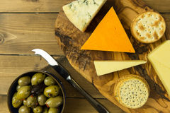 Cheese platter with olives and biscuits on wood table. Tasty cheese platter with olives and biscuits Stock Photography