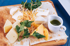Cheese platter and sauce on wooden platter Royalty Free Stock Photo