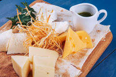 Cheese platter and sauce on wooden platter Royalty Free Stock Image