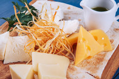 Cheese platter and sauce on wooden platter Stock Images