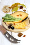 Cheese platter: solid cheese, olives, walnuts and autumn leaves Royalty Free Stock Images
