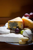Cheese platter with some organic fresh cheese. Still life with cheese and grapes royalty free stock photo