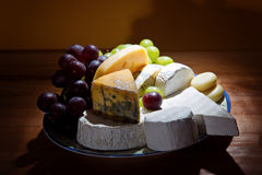 Cheese platter with some organic fresh cheese. Still life with cheese and grapes stock photography