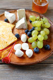 Cheese platter with two types of grapes Royalty Free Stock Photos