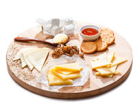 Cheese platter. Variety of cheeses accompanied by walnuts,honey, crackers and butter roll on a round wooden plate Royalty Free Stock Image