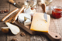 Cheese platter with wine, jam and walnuts on wooden board Royalty Free Stock Images