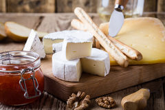 Cheese platter with wine, jam and walnuts on wooden board Stock Image