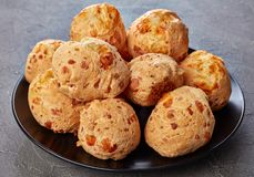Cheese puffs balls on a black plate royalty free stock image