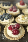 Cheese and raspberry pies. Blueberry, strawberry and pistachios tartlets on a wooden table Stock Images