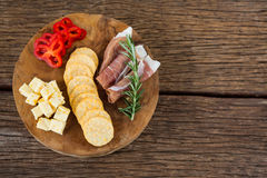 Cheese, red pepper slices, meat and nacho chips on wooden table Stock Photography