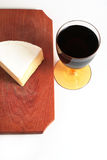 Cheese and red wine. French cheese on wood trencher with red wine cup isolated on white royalty free stock photography