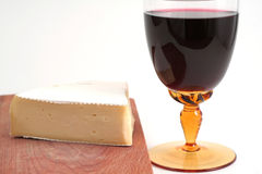 Cheese and red wine. French cheese on wood trencher with red wine cup isolated on white royalty free stock image