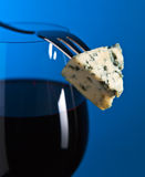 Cheese and red wine on blue background Stock Photos