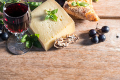 Cheese with red wine, walnuts, basil leaves and grapes Royalty Free Stock Photo