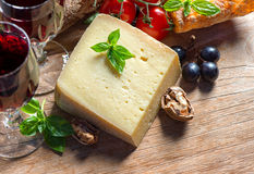 Cheese with red wine, walnuts and grapes. food background Royalty Free Stock Image