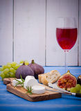 Cheese with ripe figs and wine on blue Royalty Free Stock Photos