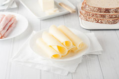 Cheese rolled up on white plate Royalty Free Stock Images