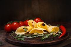 Cheese rolls on a wooden board. Cheese rolls on a wooden board with tomatoes, chili and herbs. Copy space royalty free stock image