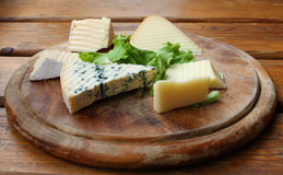 Cheese Rustic Setting. Various slices of cheese on a traditional round wooden plate Royalty Free Stock Photography