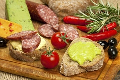 Cheese, salami and bread  on a board Royalty Free Stock Images